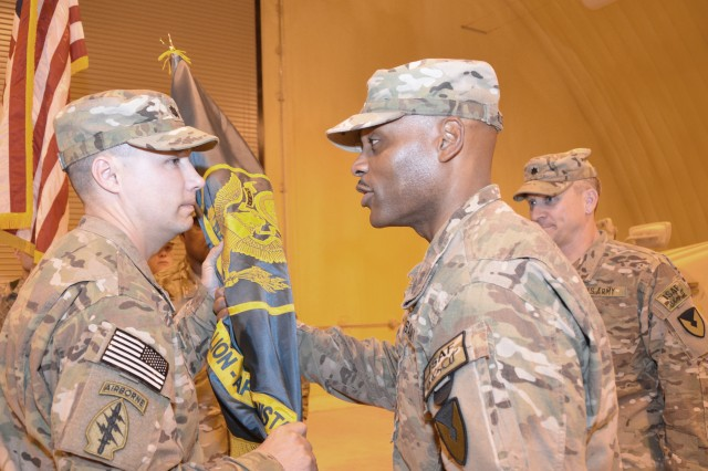 Col. Michel M. Russell, Sr., commander, 401st Army Field Support Brigade, passes the AFSBn-Bagram, 401st AFSB colors signifying the change of command to Lt. Col. Peter J. Koch, battalion commander while Lt. Col. Grant L. Morris, outgoing battalion commander looks on.