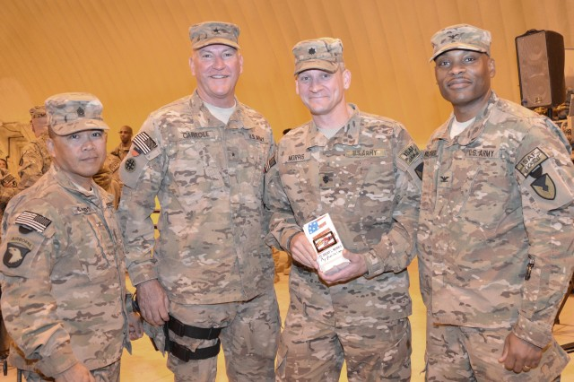 """Lt. Col. Grant L. Morris (second from right), outgoing commander, AFSBn-Bagram, 401st Army Field Support Brigade, holds a """"mini T-wall"""" gift from Col. Michel M. Russell, Sr. (far right), commander, 401st AFSB while Command Sgt. Maj. Ramon C. Caisido (far left), command sergeant major, 401st AFSB and Brig. Gen. Les J. Carroll, commander (second from left), Joint Sustainment Command Afghanistan look on."""