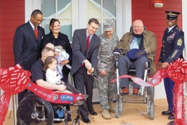 Garrison Commander Col. John Strycula and Clark Realty Capital, LLC Project Director Casey Nolan cut a ribbon Wednesday at Woodlawn Village to dedicate two new universally accessible homes as part of the Wounded Warrior Home Project at Fort Belvoir,Va. Also pictured are Ivan Bolden, chief of Public Private Partnerships, Office for the Chief of Staff for Installation Management; Marine Corps Staff Sgt. Travis Green with wife, Julie, and two of their children; Michael Graves, founding principal and lead designer of Michael Graves & Associates; and Command Sgt. Maj. Michael Williams of the U.S. Army Military District of Washington.