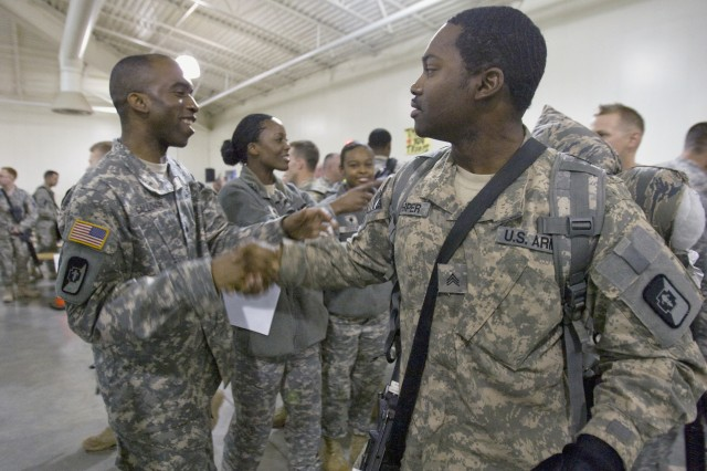 Sgt. Robert Galloway, left, 47th CSH.,62nd Med. Bde.,  greets Sgt. Anthony Harper, one of about 170 Soldiers returning to JBLM Tuesday from Iraq.