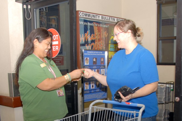 Michelyn Kea (left), administrative support clerk, Schofield Barracks Commissary, demonstrates an ID card check with Sarah Elser, family member, Dec. 5. Starting Jan. 2, military ID cards will be checked at the entrance and at the register at the Schofield Barracks Commissary.