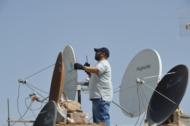 Wilton Hobbs, an information technology specialist, adjusts a satellite dish at the South District's Herat Area Office in Southern Afghanistan.