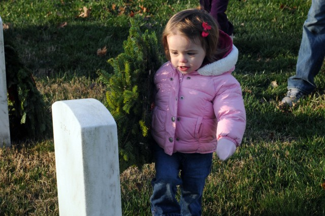 Anna, 18 months old, of Vienna, Va., lays a wreath at a grave stone at Arlington National Cemetery in Arlington, Va. This year, about 85,000 wreaths made their way from Maine to the Arlington National Cemetery to be laid by volunteers at grave stones there, Dec. 10, 2011, as part of the 20th annual Wreaths Across America event.