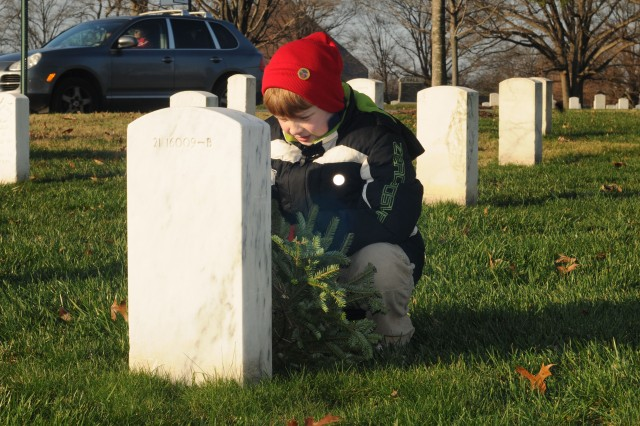 Harrison, 9, of Springfield, Va., lays a wreath at a grave stone at Arlington National Cemetery in Arlington, Va. This year, about 85,000 wreaths made their way from Maine to the Arlington National Cemetery to be laid by volunteers at grave stones there, Dec. 10, 2011, as part of the 20th annual Wreaths Across America event.