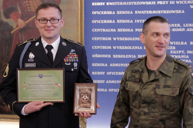 U.S. Army Staff Sgt. Tomasz Bartoszyn, 1st Battalion, 4th Infantry Regiment,  receives a plaque of appreciation from Polish Command Sgt. Maj. Marek Kajko, commandant of the Polish Land Forces NCO Academy, during a ceremony in Poznan, Poland, Dec, 9, 2011.  While Polish soldiers routinely attend the U.S. 7th Army's NCO Acdemy in Grafenwoehr, Germany, Bartoszyn is the first U.S. Soldier to attend and graduate from the Polish NCO Academy.