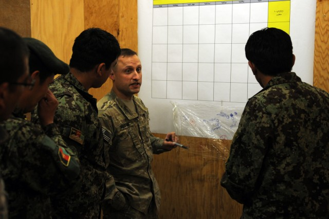 Maj. Arieyeh Austin, 2nd Battalion, 87th Infantry Regiment executive officer, teaches Soldiers in the 3rd Kandak, 205th Afghan National Army Corp how to plan operations for their Soldiers. He shows the staff officers how to make a coordinated operations calendar for the battalion.