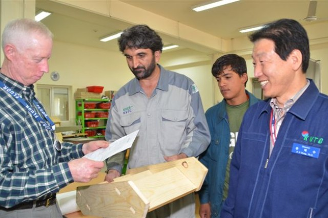 George Rabb, Fluor country project manager for LOGCAP, holds a drawing of the sample set of steps built by an Afghan student in the Korea Vocational Training Center construction class. The sample is held by one of the Afghan instructors at KVTC, while Dr. Kong Deok-soo, KVTC director, looks on.