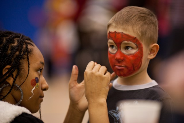Volunteer Alexis Harris, 14, paints a Spider-Man face on 3-year-old Blake Thompson of Laurel. Children also posed for photos with Santa Claus and wrote letters to deployed troops.