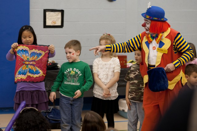 Bubbles the Clown helps children with magic tricks at the Enlisted Spouses Club's annual Children's Holiday Party on Saturday. More than 275 people attended the event.