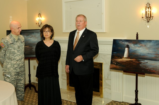 Senior APG commander Maj. Gen. Nick Justice, left, Anna Justice and Ed Carnes, chairman of the Fisher House's Support Our Heroes Ball committee, present the Pooles Island Lighthouse painting Dec. 9 at Top of the Bay at Aberdeen Proving Ground, Md.