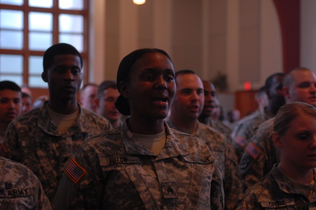 Sgt. Sherry E. Futch, a native of Charlotte, N.C., now a human resources specialist assigned to Headquarters and Headquarters Company, 13th Combat Sustainment Support Battalion, 593rd Sustainment Brigade, and other Soldiers recite the Creed of the Non-Commissioned Officer during the battalion's NCO induction ceremony at Evergreen Chapel, Dec. 9, on Joint Base Lewis-McChord, Wash.  Futch was one of 26 Soldiers to be formally inducted into the corps of NCOs.  Last month, she successfully completed the Warrior Leaders Course at the Henry H. Lind NCO Academy, and was selected for the Commandant's List for earning a grade point average in the top 20% of her class during the three-week long course. (Photo by Sgt. Kendra McCurdy)