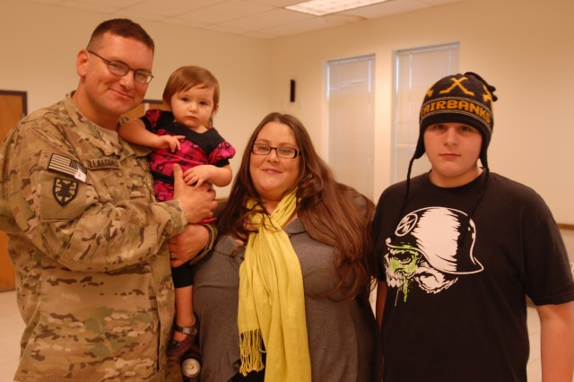 "Sgt. Lorenzo Z. Villalobos Jr., a native of San Diego, now a postal clerk assigned to the 22nd Human Resources Company, 593rd Special Troops Battalion, 593rd Sustainment Brigade here, poses for a photo with 14-month old daughter, Aria Bella, wife Michele, and 13-year-old son Tristan, following a welcome home ceremony for Villalobos' platoon, ""Uniform 4,"" Dec. 9, on Lewis-North, Wash.  Villalobos was one of 20 Soldiers who returned to Joint Base Lewis-McChord, Wash., following a yearlong deployment to Afghanistan. (Photo by Sgt. Kendra McCurdy)"