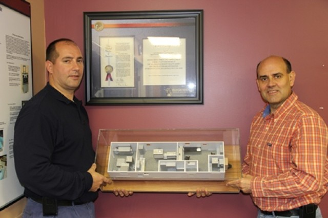 Mechanical engineer George Noya, team leader for the Mobile Labs and Kits Team, and senior mechanical engineer Luis Enrique Faure display a model of the All Hazards Receipt Facility. The AHRF patent is hanging on the wall behind them.
