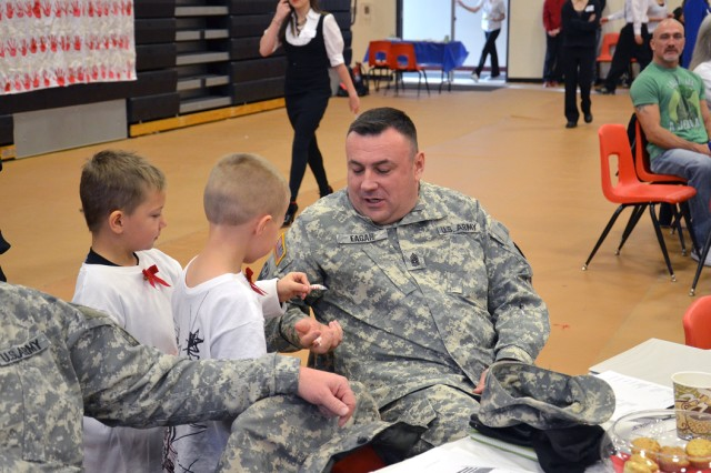 Command Sgt. Maj. Thomas L. Eagan, command sergeant major, 1st Space Brigade, receives a small thank you from two Peyton kindergarteners during the 12th Annual Veteran's Breakfast on Dec. 5 at Peyton High School.