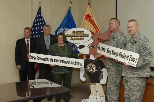 "Winners of the Rock Island Arsenal Energy Conservation mascot and slogan design contest goes to two individuals from First Army. Melody McHugh, First Army chaplain's secretary, won for her mascot design with ""Rocky"" the Rock Island Arsenal Energy hound. The slogan recipients tied for the honors. Master Sgt. Ted Scully, First Army chief paralegal noncommissioned officer, submitted the slogan, ""Energy conservation, the smart weapon in our Arsenal!"". Mark Schneider, from the Joint Munitions Command, also won with ""Be a hero - keep energy waste at zero!"". Each of the awardees were presented a First Army coin from Brig. Gen. Kendall Penn, First Army deputy commanding general - operations, and a $100 check from the Stone Hill Energy Company."