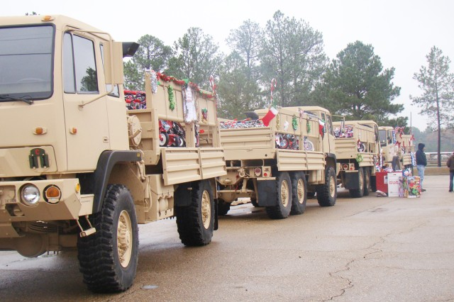 A line of Family of Tactical Vehicles wait to be unloaded at Red River Army Depot's annual Toys for Tots campaign. Employees donated 500 bicycles, more than 1,350 toys and 6,200 non-perishable food items toward the local campaign.
