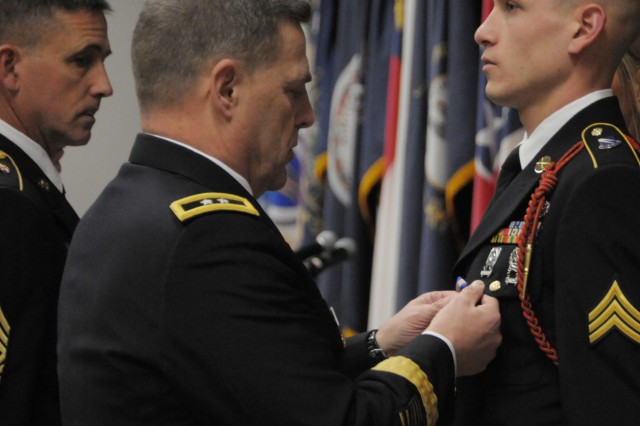 Maj. Gen. Mark A. Milley, Fort Drum and 10th Mountain Division (LI) commander, pins Sgt. Jacob J. Perkins with the Soldier's Medal during a large gathering held Tuesday at the Multipurpose Auditorium at Fort Drum, N.Y.