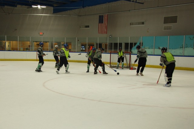 """SURROUNDING THE GOALIE: The officers come in for the """"kill"""" as they surround the enlisted team's goalpost. It was enlisted (in green vests) vs. officers on the ice for a """"friendly"""" game of broomball. The officers won 18-4."""