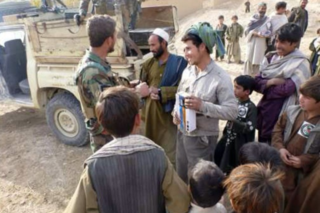 An Afghan National Army Special Forces commander hands out radios to locals after the completion of a bridge assessment in Qasamabad village, Day Kundi province, Dec. 10.  ANASF and coalition Special Operations Forces assessed the condition of the bridge to determine possible ways to improve upon the structure.