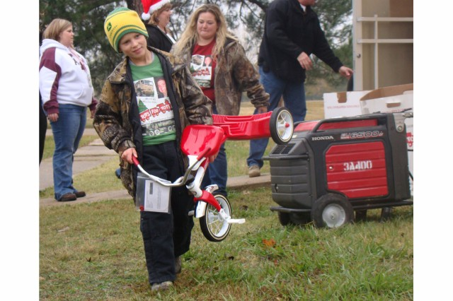 Skylar Taylor lends a hand and carries a tricycle for loading as his mother, Crystal Taylor, follows him. Skylar donated his entire piggy bank savings to this year's campaign in memory of Ryan Johns.