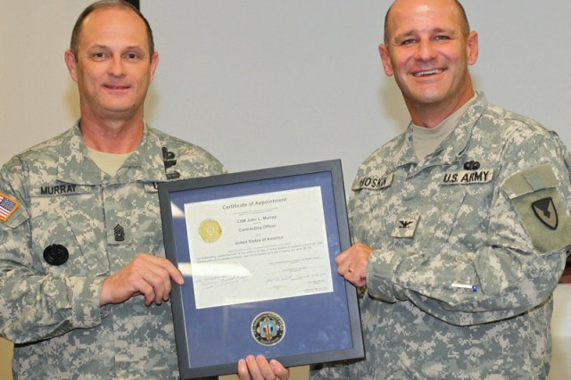 "Col. Michael Hoskin (right), commander, 413th Contracting Support Brigade, presents Command Sgt. Maj. John L. Murray, Army Contracting Command, with a ""CSM Dime Special Warrant"" for his support to the 413th acquisition community ""authorizing"" him to issue U.S. government contracts obligating up to and including 10 cents."