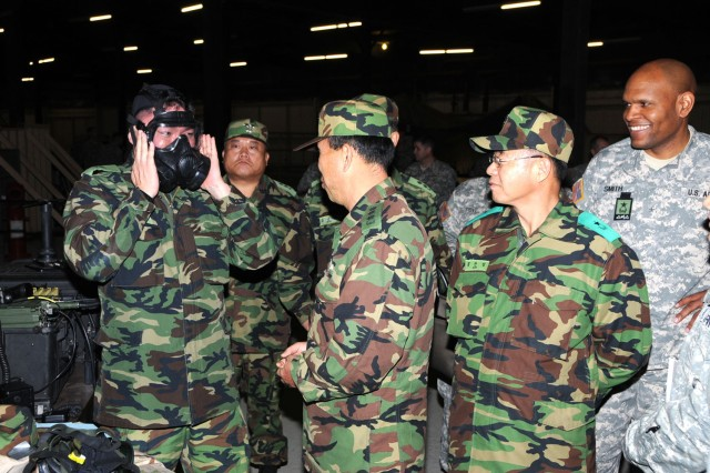 Maj. Ki Chul Kim, an operations planning officer with the Republic of South Korea's Chemical, Biological, and Radiological Defense Command tries on a mask during a capabilities exercise Dec. 5 at APG's Warrior Training Center. The CAPEX was part of a weeklong visit by 10 Korean soldiers to the 20th Support Command (CBRNE).