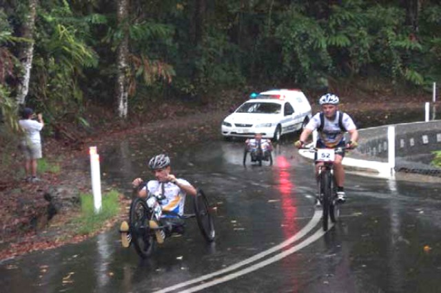 Carlos Moleda, Andrew Chafer and Patrick Doak (from front to back) race on slick, wet roads on day one of the 10-day, 760-mile Crocodile Trophy in Queensland, Australia. Corps team member Herman Kramer accompanied the cycling team as a crew member and followed the riders in the support vehicle (background) to provide food, water and motivation.