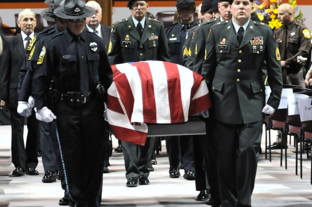 Soldiers from the 424th Transportation Company and Virginia Tech police officers carry the casket of retired Staff Sgt. Deriek Crouse out of the Cassell Coliseum at the conclusion of his funeral. Crouse, a Virginia Tech police officer, was killed in the line of duty Dec. 8.