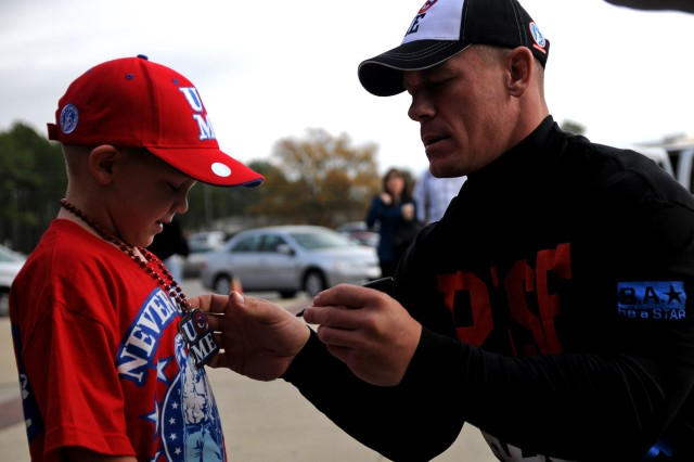 "John Cena, a World Wrestling Entertainer Superstar, signs a little boy's Cena apparel during the WWE's Superstars and Divas visit to Fort Bragg, N.C., Dec. 9-10, 2011. More than twenty Superstars and Divas went around the post taking pictures and signing autographs for Soldiers and families leading up to their free ""Tribute to the Troops"" show Sunday evening at the Crowne Coliseum in Fayetteville, N.C."