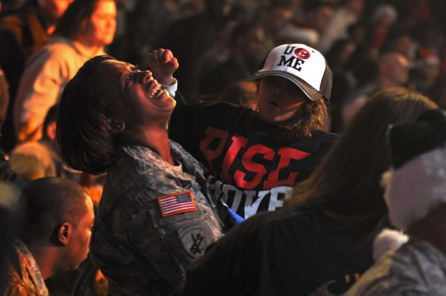 "Spc. Ashley Stewart, a medic with 44th Medical Brigade, and daughter Khalia, 4, dance during Nickleback's performance at the World Wrestling Entertainment's free ""Tribute to the Troops"" show Sunday evening at the Crowne Coliseum in Fayetteville, N.C. More than twenty WWE Superstars and Divas went around Fort Bragg, N.C., taking pictures and signing autographs for Soldiers and families Dec. 9-10, 2011."