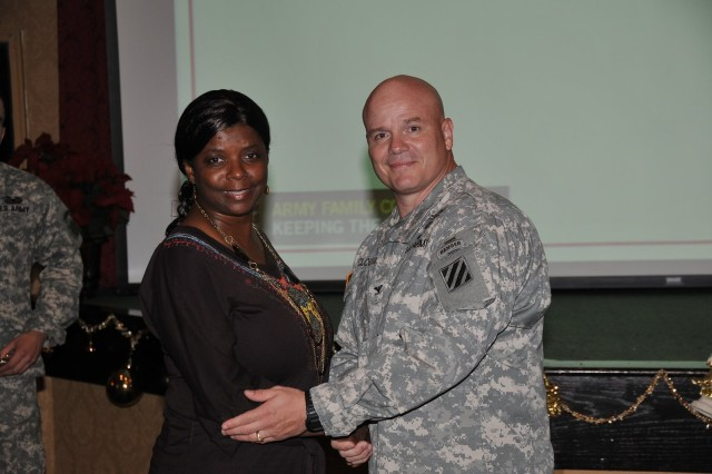 Deputy Commanding General-Operations Col. Roger Cloutier warmly congratulates ICE Hero, Barbara Williams of Family and Morale, Welfare and Recreation Pass and Permit office.