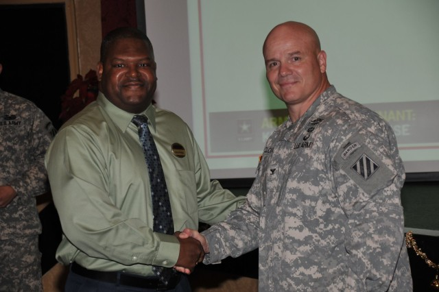 Deputy Commanding General-Operations Col. Roger Cloutier warmly congratulates ICE Hero James Fleming, resiliency trainer with Army Community Service.