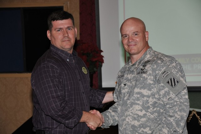 Deputy Commanding General-Operations Col. Roger Cloutier warmly congratulates ICE Hero Richard Johnson, resiliency trainer  with Army Community Service.