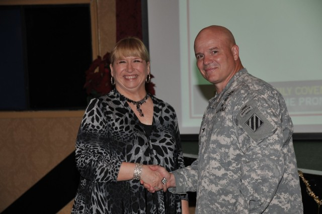 Deputy Commanding General-Operations Col. Roger Cloutier warmly congratulates ICE Hero Dorothy Taylor with Directorate of Human Resources education services office.