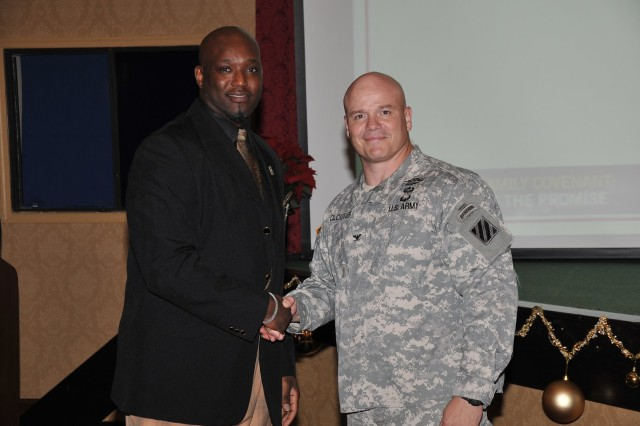 Deputy Commanding General-Operations Col. Roger Cloutier warmly congratulates ICE Hero Bobby Johnson with Directorate of Human Resources retirement services office.
