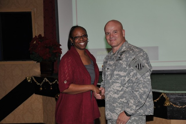 Deputy Commanding General-Operations Col. Roger Cloutier warmly congratulates ICE Hero Cynthia Turner with Non-Appropriated Civilian Personnel Advisory Center.