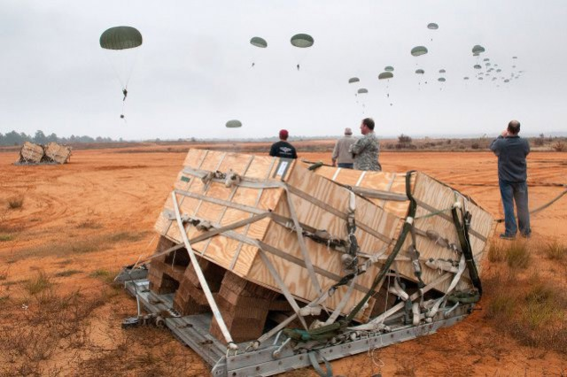 Container Unitized Bulk Equipment, or CUBE, crates rest in the foreground after a test airdrop Nov. 10, 2011, at Camp MacKall, N.C. The CUBE system will deliver water and fuel to remote forward operating bases.