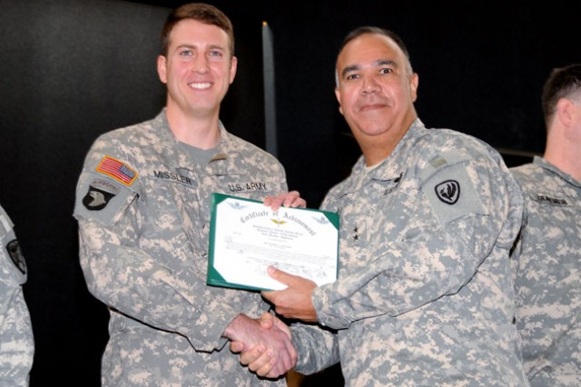 Maj. Gen. Anthony G. Crutchfield, U.S. Army Aviation Center of Excellence and Fort Rucker commanding general, presents CW2 Nicholas A. Missler, Officer Instructor Pilot of the Year, with an award certificate during the ceremony at the U.S. Army Aviation Museum Dec. 13.