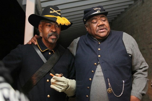 "Kenneth Reese and Wallace Moore, Fort Sill Museum living history interpreters, portray Buffalo Soldiers from the 10th Cavalry Regiment at the Cavalry Barracks during the candlelight stroll Dec. 11. Moore said if you sit quietly on the porch of the barracks on Christmas Eve you can hear tin cups rattle and old Soldiers harmonizing: ""Sleep in heavenly peace, sleep in heavenly peace."""