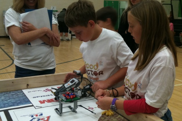 Christopher Miller and Ashley Hall of Gen. Myer Elementary School make final preparations to RAWBY as their teacher, Suzi Szymeczek, looks on. RAWBY is the robot the Myer students created using Legos®.