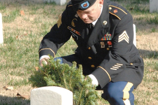 Sgt. Ron Dail, 59th Ordnance Brigade, places a holiday wreath on a grave at the national cemetery.