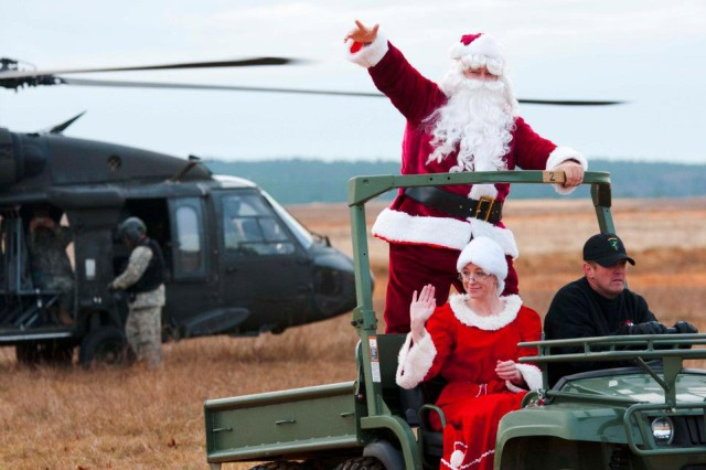 Santa and Mrs. Claus make a grand entrance on their sleigh, a UH-60 Black hawk, as they land on Sicily Drop Zone, Saturday. Operation Toy Drop is a Family-friendly event; spouses, children and friends gathered at a viewing area on the drop zone to watch their loved ones earn their set of international airborne wings.