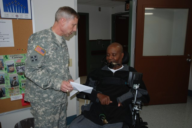 "FORT EUSTIS, Va. -- The U.S. Army Soldier's Creed contains the phrase, ""I will never leave a fallen comrade."" Putting words into action, Brig. Gen. Peter Utley, U.S. Army Training and Doctrine Command, meets veteran Christopher Johnson and shares a holiday card during a visit to the Veterans Affairs Medical Center in Hampton, Va., Dec. 8. Utley thanked all veterans he met for their service and sacrifice and encouraged other Soldiers to visit VA patients not only this holiday season, but throughout the year. (U.S. Army photo by Greg Mueller)"
