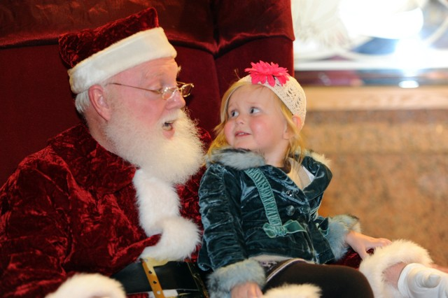 Amara Campbell, granddaughter of Lt. Gen. Don Campbell Jr., III Corps and Fort Hood, Texas, commanding general, sits on Santa's lap during the III Corps Headquarters Christmas Tree Lighting Ceremony Dec. 7, 2011.