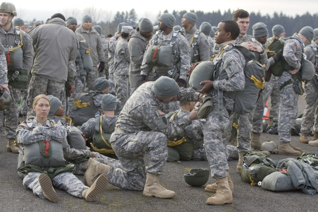 1st Specials Forces Group Soldiers break into buddy teams to safety-check parachutes before the jump with the Canadian Special Operations Regiment Dec. 8, 2011, at Rogers Drop Zone on Joint Base Lewis McChord, Wash.