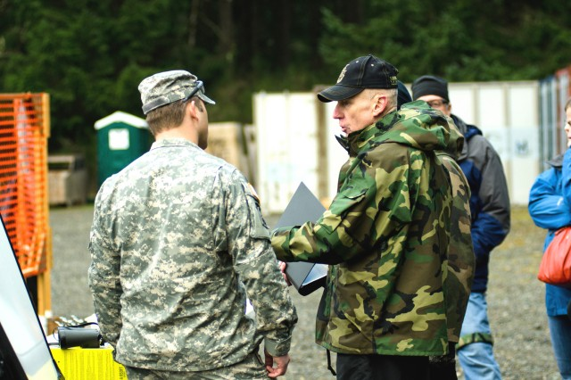 Rich Wall, right, an Army Special Forces veteran, shares a bit of history at Flat Range Complex at Joint Base Lewis-McChord, Wash., Dec. 7, 2011. During two days of weapons shoots for family and friends of 1st Special Forces Group, hundreds of individuals got the chance to fire as part of Menton Week.
