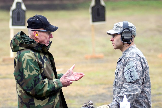Rich Wall, an Army Special Forces veteran, speaks with one of the unit's current Soldiers at Flat Range Complex at Joint Base Lewis-McChord, Wash., Dec. 7, 2011. Family members and friends of Special Forces Soldiers fired weapons after safety briefings as part of Menton Week, Dec. 5-9.