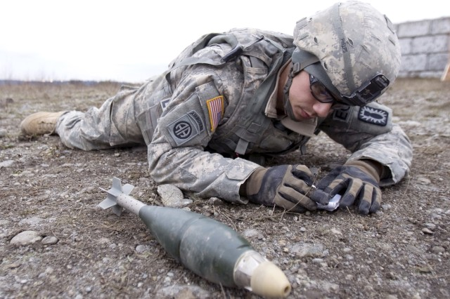 Staff Sgt. Christopher Phelps, from Fort Campbell, Ky., closely examines an 81mm mortar round as he prepares to safely explode the device.