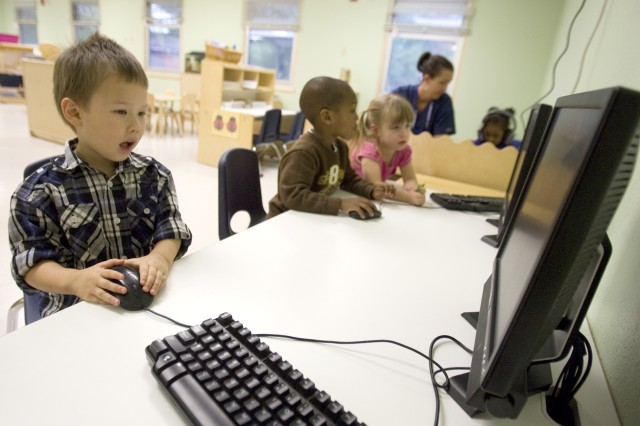 Savien, left, Bray, center and Audrey, try out the new computers at the recently reopened Beachwood Child Development Center on Joint Base Lewis-McChord, Wash., Lewis North.