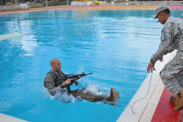 """SCHOFIELD BARRACKS, Hawaii """" First Lt. Phillip Baweja, a platoon leader for A Company, 1st Battalion, 14th Infantry Regiment, 2nd Brigade Combat Team, 25th Infantry Division, jumps into the pool with a vest and dummy M4 carbine as part of the combat water survival test during the Best Ranger Competition tryouts Dec. 7 at Schofield Barracks, Hawaii. The tryouts will yield the Soldiers that will represent the 25th Infantry Division at the annual Best Ranger Competition at Ft. Benning, Ga., in April 2012."""